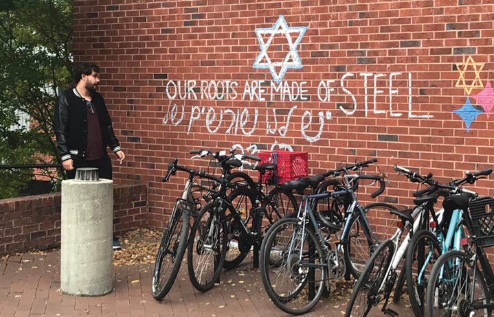 "A student stands next to ICC, where the words ""Our roots are made of steel"" are scrawled in chalk. Image courtesy of Natalie Ise, The Hoya."
